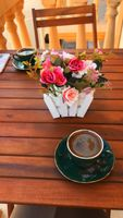 Turkish coffee in green cup and flowers on the table
