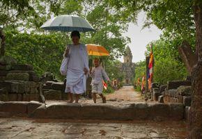 Bakong – nun and boy walking with umbrellas
