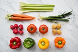 Fresh vegetables arranged on chopping board flatlay