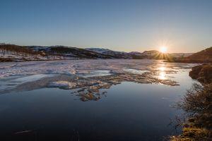 Midnightsun behind ice covered lake