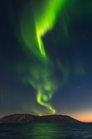 Northern Lights above high mountains out in Altafjord