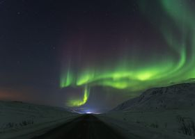 Northern lights Finnmark Norway above road in winter with snow