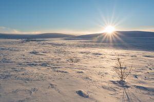 Sunshine just above flat mountain horizon with snow