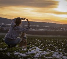Owner showing love with his Labrador Retriever with sunset background