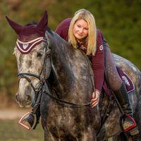 Blonde woman riding grey horse