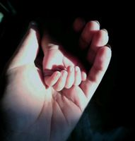 Baby's hand on mother's hand