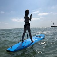 Paddle boarding on a lake with the clouds and blue sky