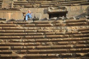 The man sitting in the amphitheater in Bosra