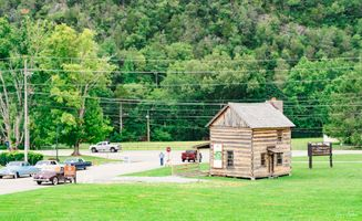 Vintage Cars on Display near a Log Cabin Museum
