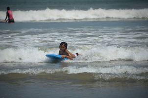 A little kid is surfing