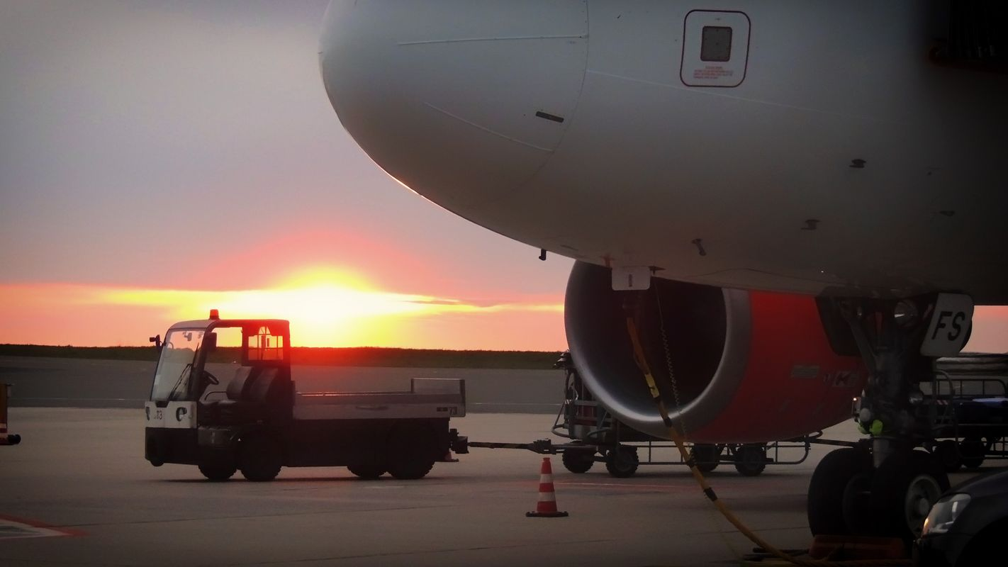 Beautiful sunset behind an easy jet plane and a baggage trolley at the german airport in dortmund