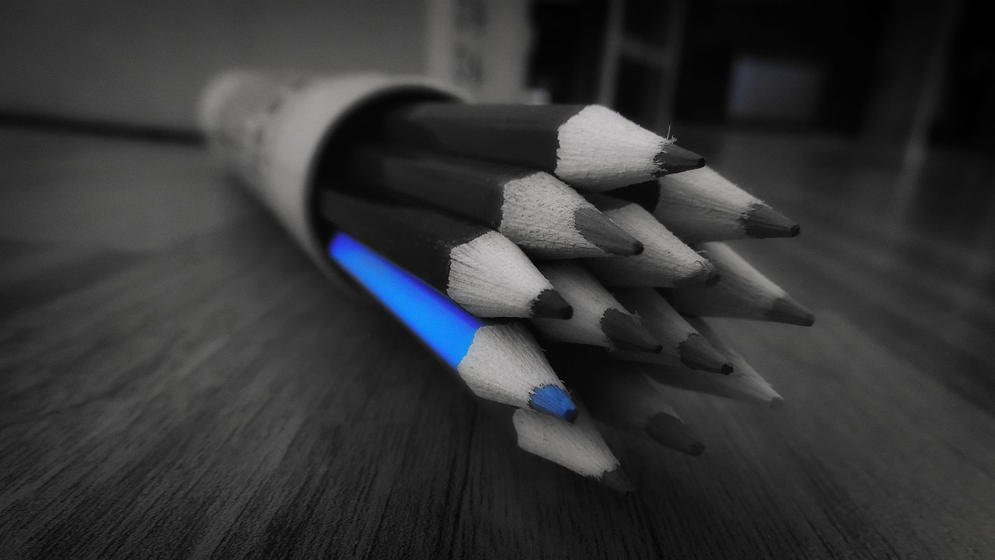 Black and white photo of coloured pencils with a blue coloured pencil highlighted in blue