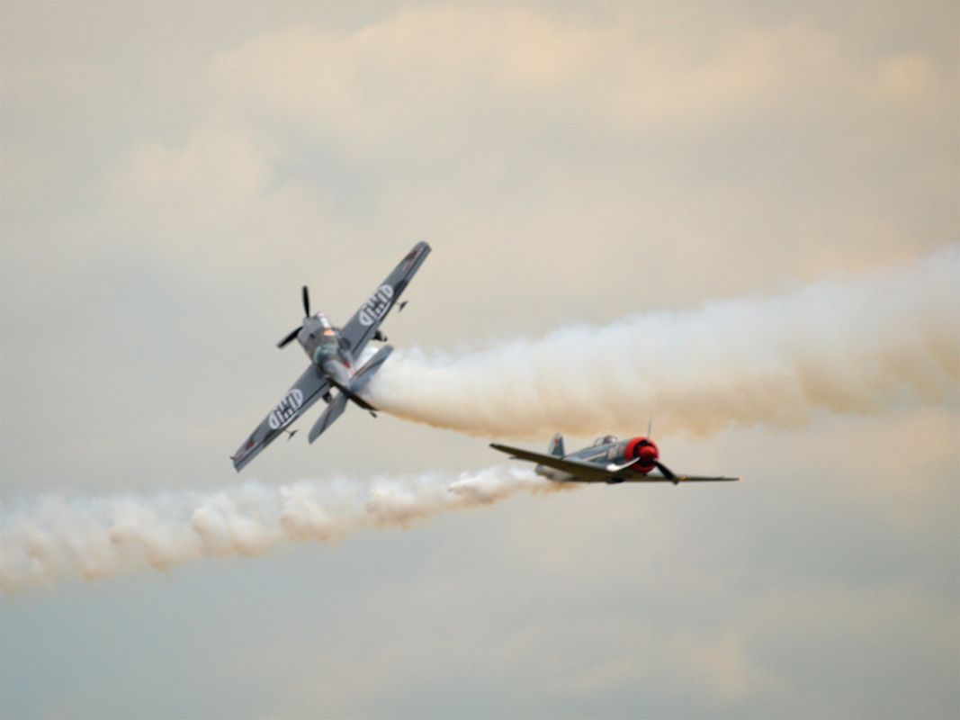 Two planes pass each other very closely with smoke trails