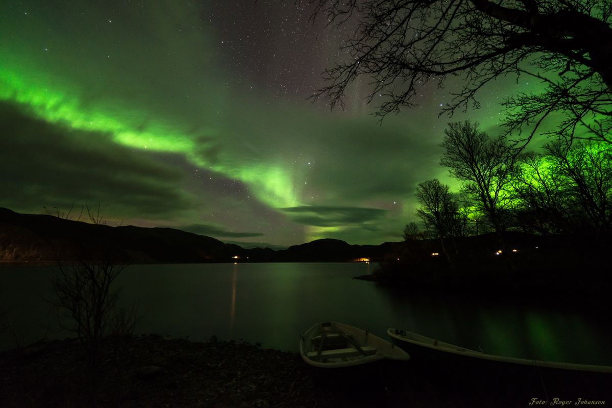 Northern Lights above a lake with boats