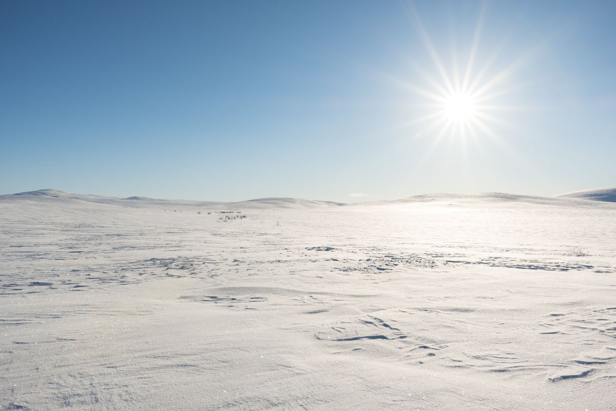 Flat snow covered mountain with sun shining