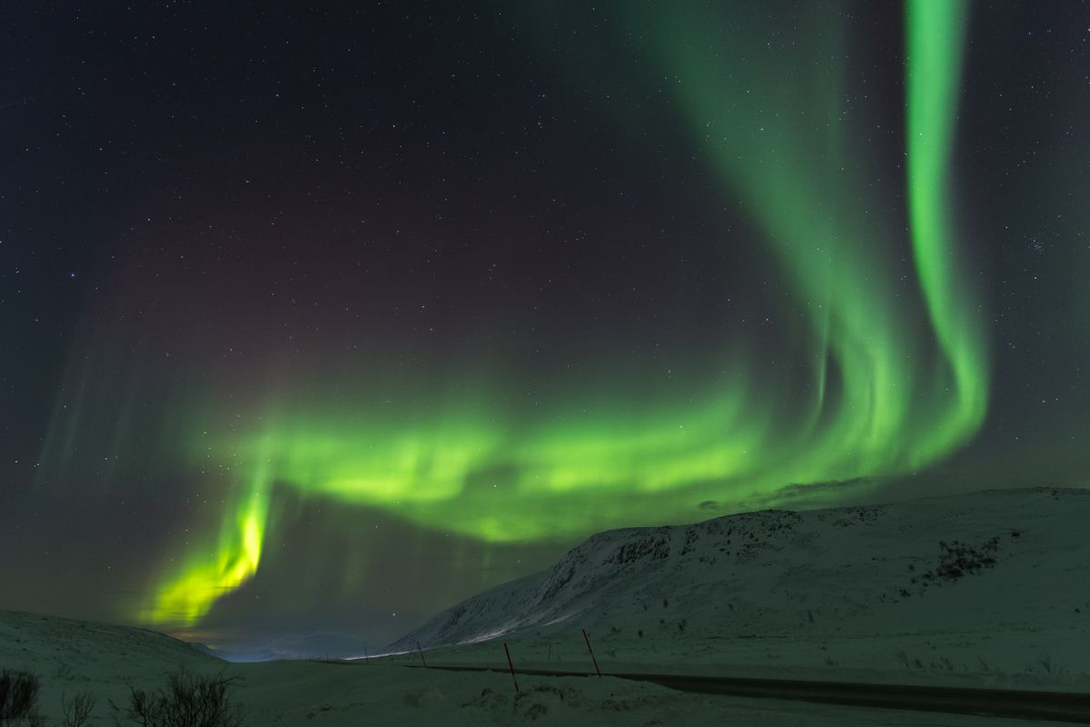Northern lights Finnmark Norway above road and mountain