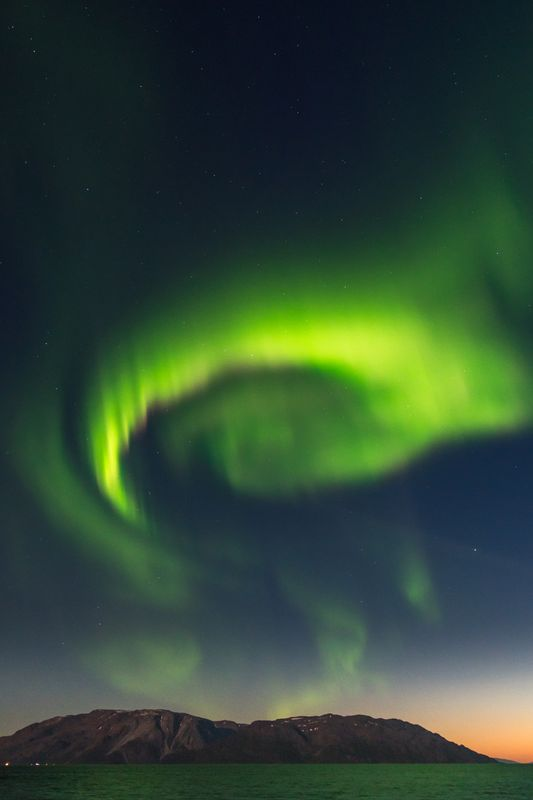 Northern Lights half circle above high mountains out in Altafjord