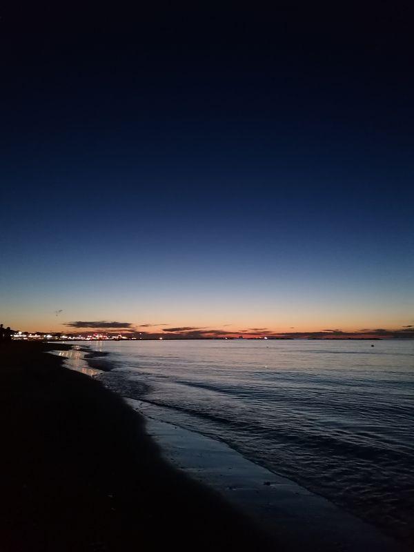 Tramonto in spiaggia con le nuvole all'orizzonte