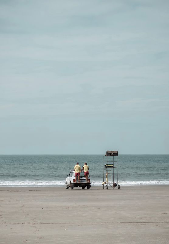 Two man sitting on a car and watching the ocean