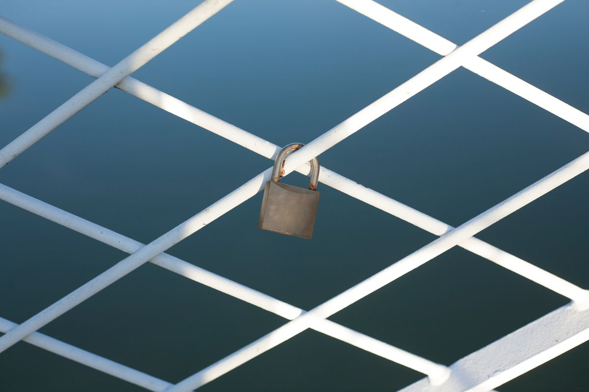 A padlock locked around the bridge fence