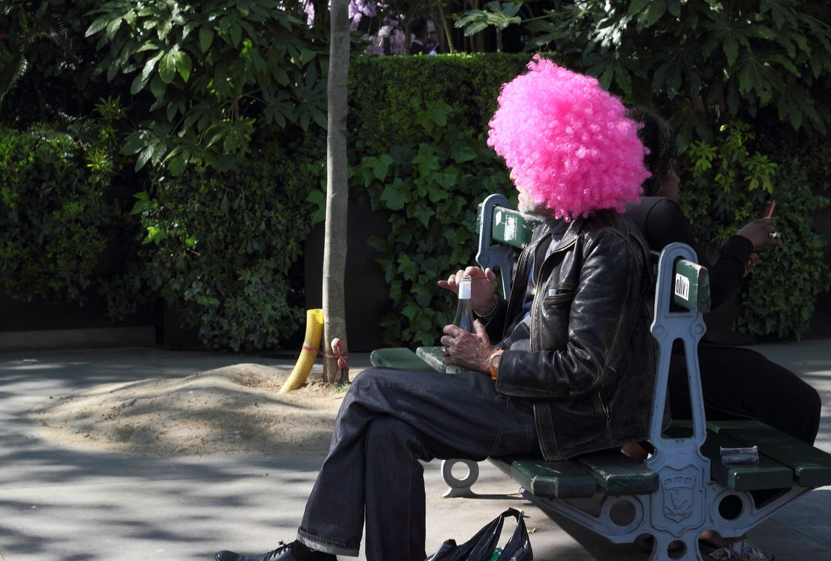 Man with pink hair and a bottle