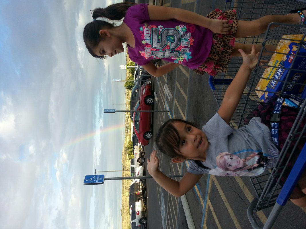 2 girls pose in a shopping cart