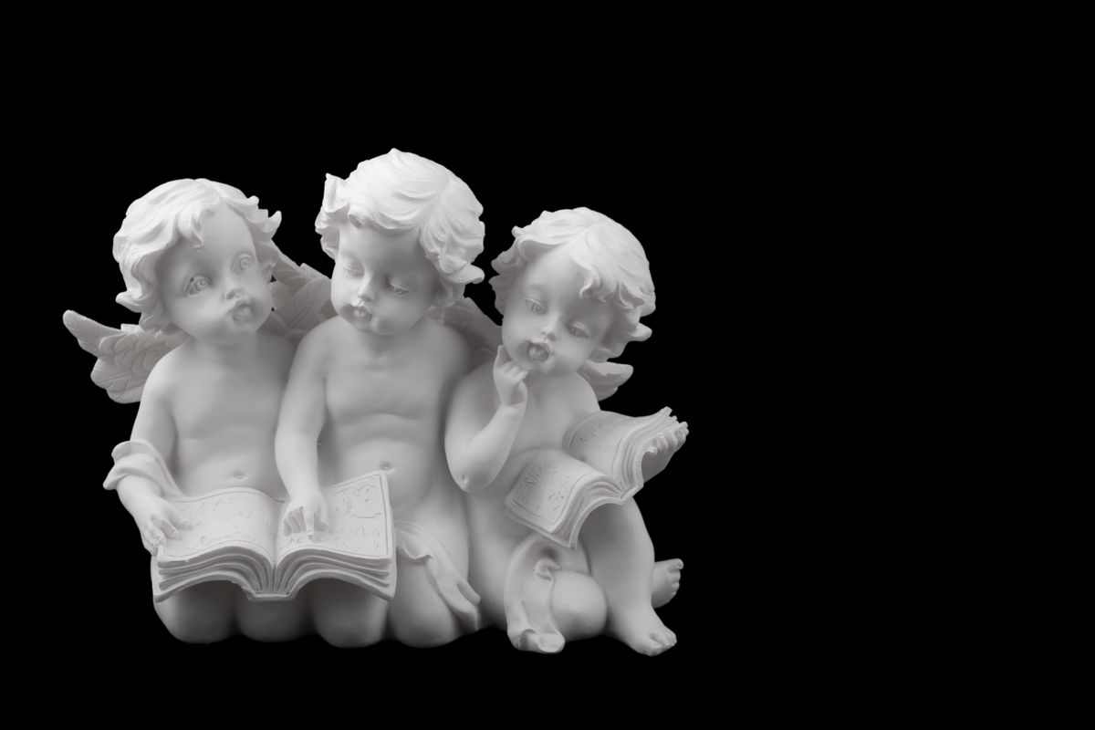 Three ceramic white angels read the book
