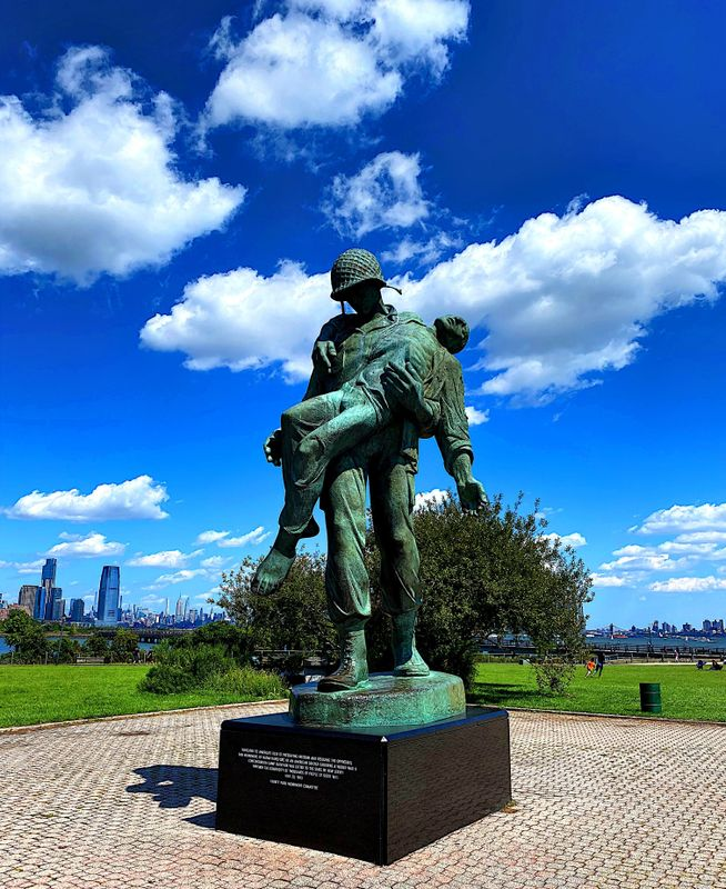 A sculpture depicting an American soldier carrying a concentration camp survivor against the New York City skyline background