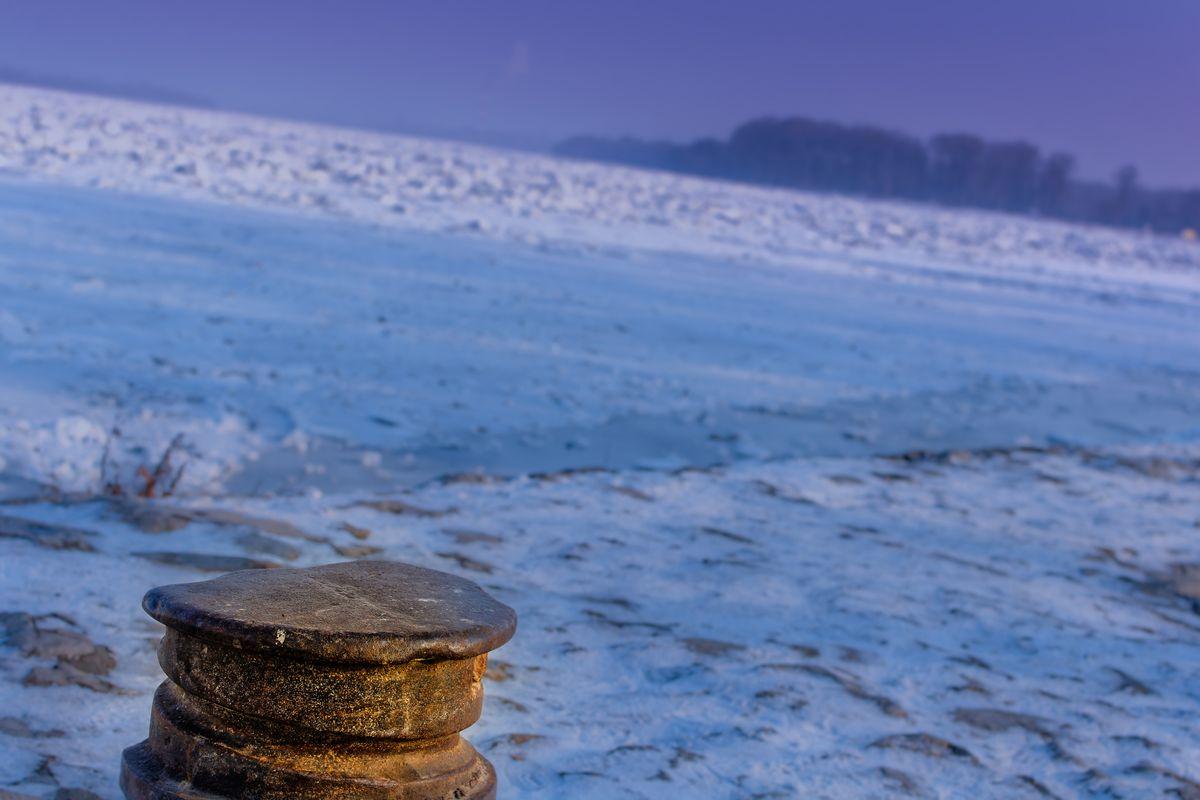Bollard by the frozen river