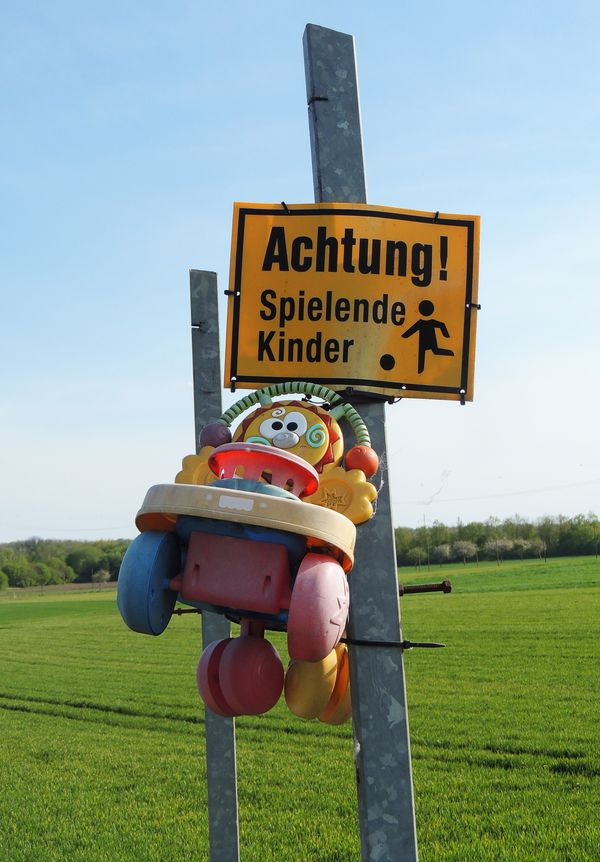 Funny road sign in front of a farm watch out for playing children