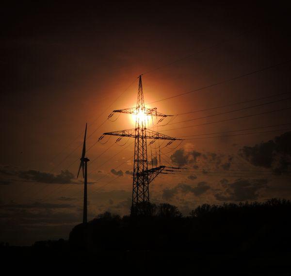 Sunset behind a power pole overhead line mast and an energy wind turbine