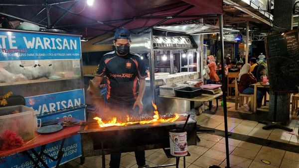 A guy at a food stall grill the satay kitchen