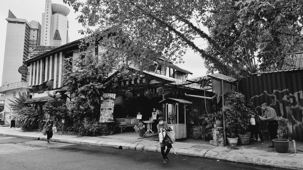 Black & white photo of people walking on the street outside of an old building cafe