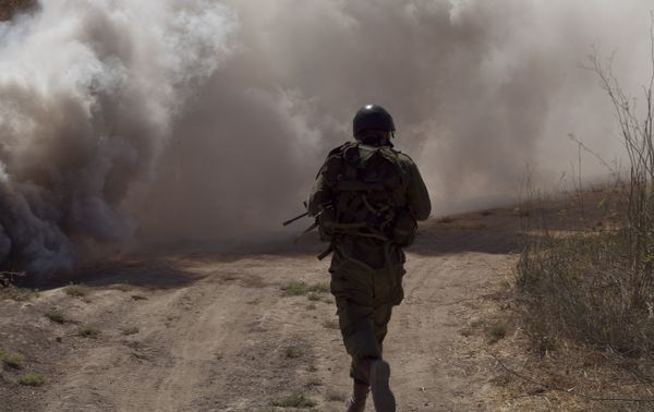 A soldier ran through thick smoke