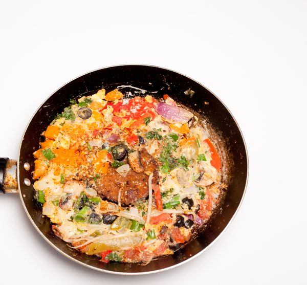 Vegetable omelet in a black iron pan On a white background