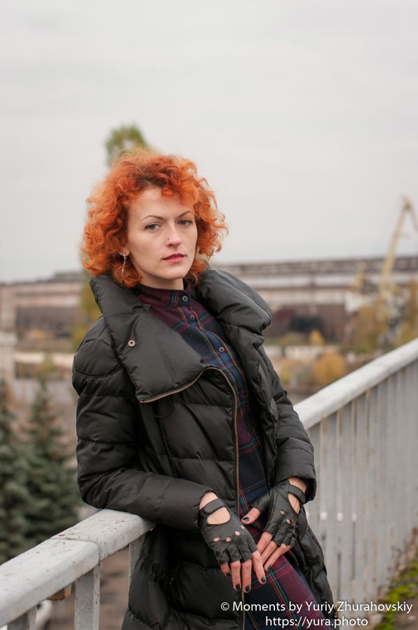 Red haired female in an abandoned area near a bridge