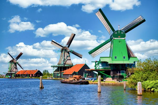 Dutch windmill in green countryside close to Amsterdam, Netherlands, with blue sky and river water.