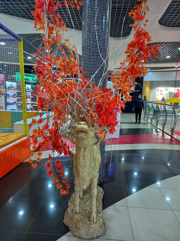 A sculpture of a white deer in a shopping center, decorated in autumn motifs.