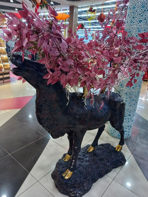 A sculpture of a black deer in a shopping center, decorated in autumn motifs.